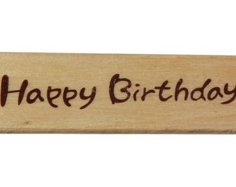 "A wooden pattern writing ""Happy Birthday"" stamp"