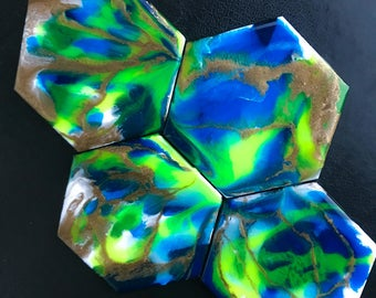 Four hexagonal wooden coasters with neon green, fluorescent blue and shimmering gold accents with a glossy resin finish