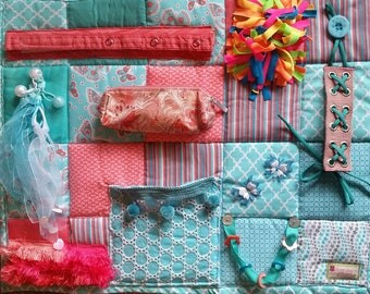 Fidget Blanket in soothing Aqua and Coral colors with many activities and textures