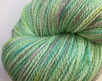 100g skein of merino and bamboo blend 4ply knitting wool yarn in green with purple, yellow, and blue hand painted spots