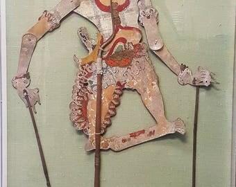 An antique Javanese encased Wayang Kulit figure
