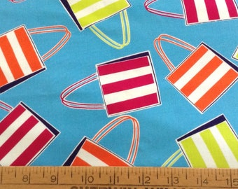 Tossed beach bags on blue background cotton fabric by the yard