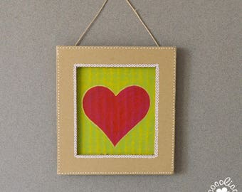 Cardboard frame painted red heart on green background