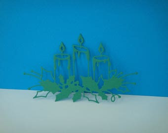 Cut out of 3 candles on green Holly leaves