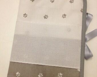 Health book has cross-stitch, grey dog paws