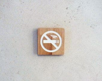 Wooden sign with engaved no smoking logo