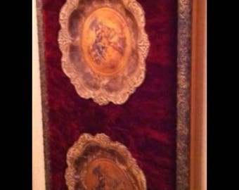 A statement brass wall panel with velvet and 2 elegant antique English decorative plates.