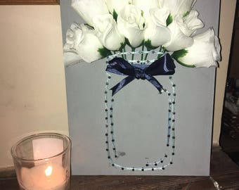 Mason jar with artificial white flowers