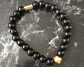 Handmade beaded bracelet in black with golden accents.