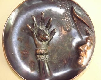circa 1970s molded copper tray face in profile hand holding a bird - charity for animals