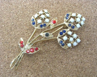 Graceful gold tone flower pin brooch with red, white, blue accents
