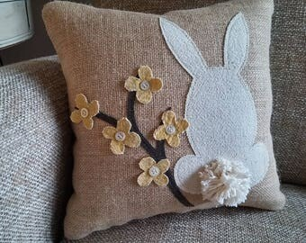 Small decorative natural burlap front pillow featuring a bunny and a flower branch