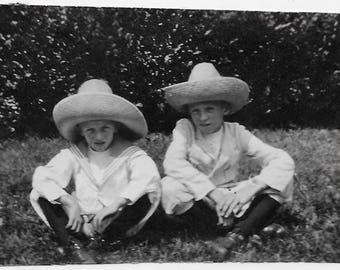 Old Photo Girl and Boy wearing Hats sitting on Lawn 1910s Photograph Snapshot vintage