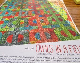 """Paper pattern for a quilt called Ovals in a Field designed by Malka Dubrawsky 65"""" x 94"""" featuring poems from pebbles fabric by Moda"""