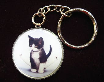 "Keychain ""Kitten gymnast"" set in resin on a support key chain, nickel - diameter 30 mm"