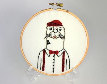 Hipster Otter Hoop Art - Hand Embroidered Otter Wall Hanging - Otter with an anchor tattoo wearing a flat brimmed baseball cap bowtie