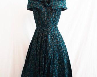 Late 1950s Teal Blue Black Gold Satiny Cocktail Dress Box Pleats Rosette Shawl Collar Dress