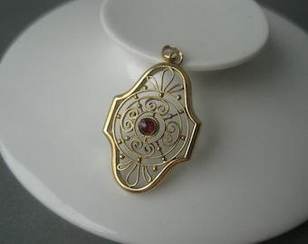 Beautiful antique Art Nouveau 14 karat solid gold pendant with a garnet.