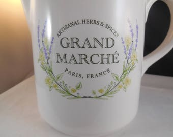 Ceramic pitcher white with delicate design of purple and green plants.  This pitcher would look great luster to the finish.