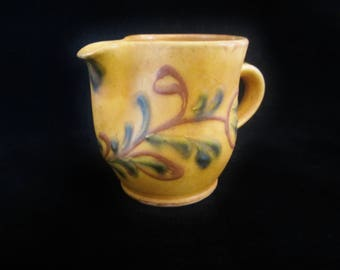Folk-Art Pottery Creamer/Pitcher - mustard yellow with floral design in rust brown and green. Stamped with makers mark.  Quirky collectible!