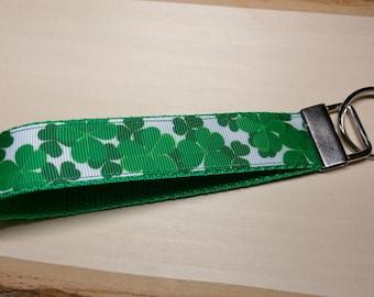 Clover, Shamrock Keychain Wristlet Key Fob.  Wrist lanyard. Green strap, white ribbon with green clovers, shamrocks.