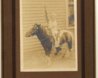 Child on pony with flag American old photo antique vintage