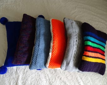 Colourful knitted cat cushions