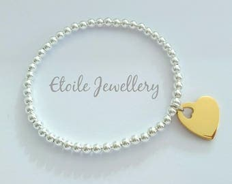 Silver beaded bracelet with a yellow gold heart
