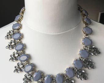 Bib style statement necklace with grey and clear stones on an antiqued chain