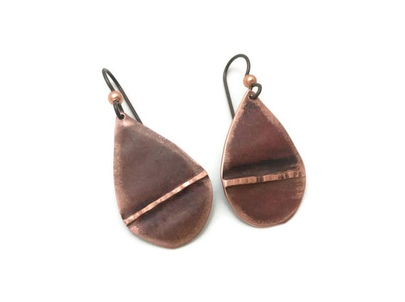 Copper teardrop earrings with an abstract folded line