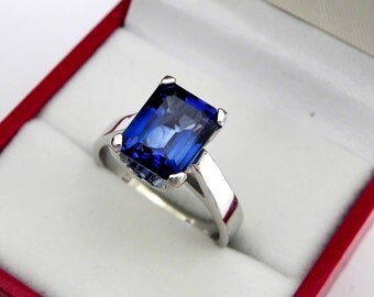 AAAA Blue Manmade Sapphire   10x8mm  4.50 Carats   in a 14K White or Rose gold cathedral style engagement ring.  1911