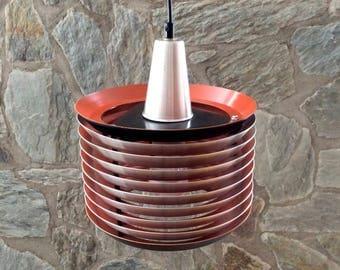Lakro mid-century Danish-style layered slats aluminum pendant light with black edges and orange inner.