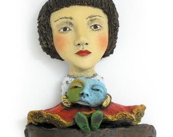 "Title: ""Choosing My Disguise""  Wall mount ceramic sculpture, 19"" x 6"" x 3"""