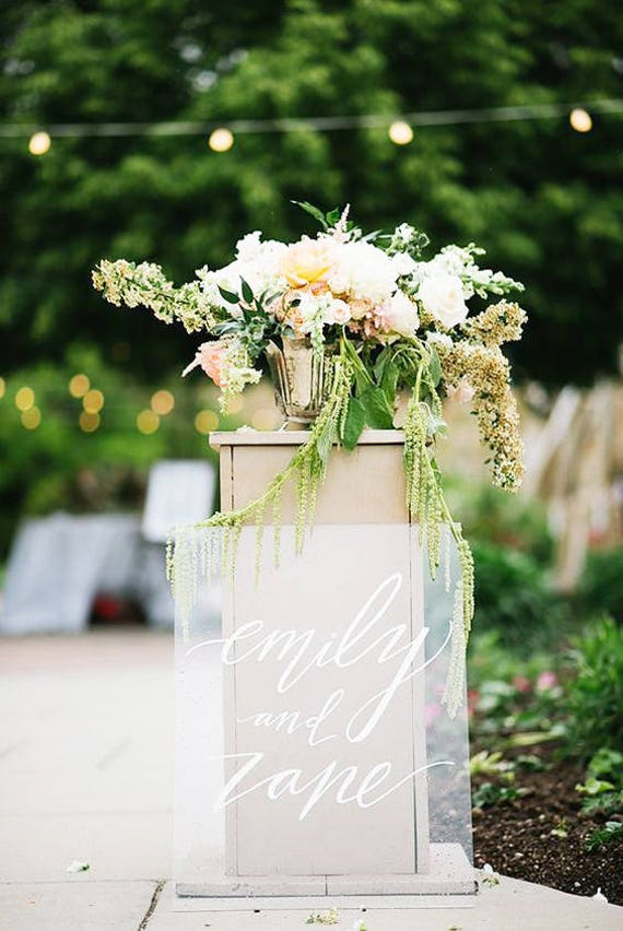 acrylic sign leaning against wedding alter with floral arrangement