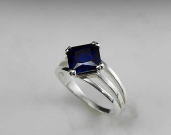 Solitaire Princess cut Blue Sapphire in a prong set gold ring
