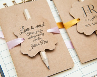 50+ Kraft wedding favours. Mini notebook favours with printed tags, ribbons and pencil. Notebook favours. Custom wedding favour place cards.