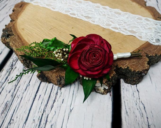 Rose flower wedding boutonniere in shades of dark wine and green