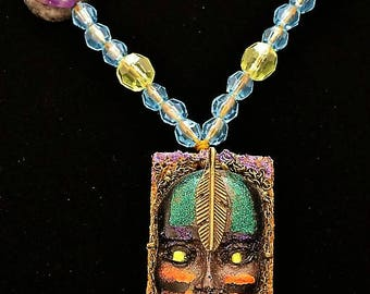 Native American Curse Breaking Mask made into a Powerful and Magick filled Pendant Back is Lava Rock,Bronze Feather, Hand made mask, enamel