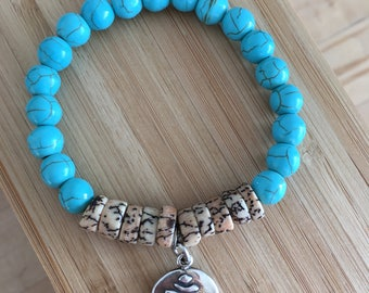 Turquoise dyed howlite bracelet with silver yoga (aum symbol) charm