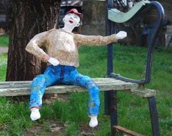 A curious figure sitting in papier mache