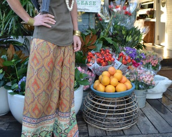 Wide-legged green/orange patterned pants with patterned trim and elasticated waist