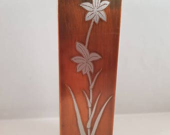 Copper vase with white metal inlay.