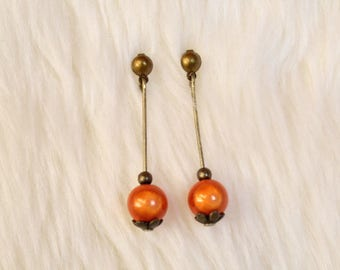 Earrings on post and orange magic pearls