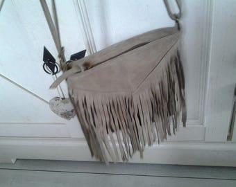 Bag has a fringe suede beige shoulder strap