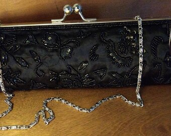 Black clutch, glass beads with removable chain.Sleek, classy! Use day or night! Perfect condition!