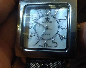 Very attractive mop dial on this Cannes quartz watch. Squared silver tone case w black/gray accented material & leather? Band
