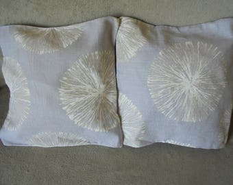 Two cushion covers printed beige and white dandelion on a grey/purple background.