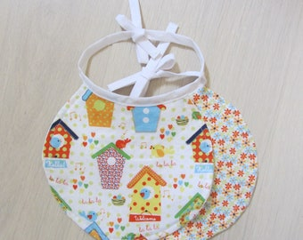 Set of two round bibs with birdhouses and flowers