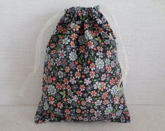 pouch made with fabric filled with grey and orange flowers