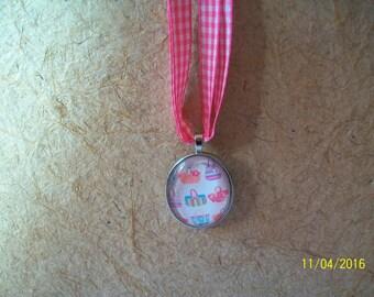 silver color pendant and a glass cabochon
